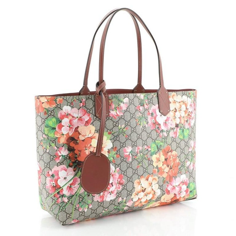 This Gucci Reversible Tote Blooms GG Print Leather Medium, crafted from blooms GG print leather, features tall leather handles and subtle Gucci logo. Its wide top opens to a reversible purple leather interior.   Estimated Retail Price: