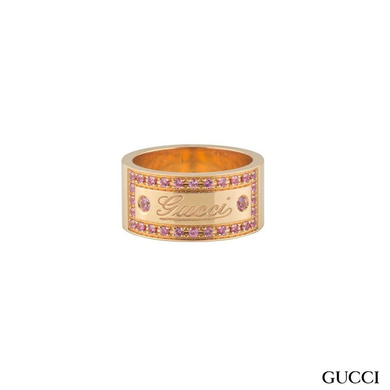 A beautiful 18k rose gold spinel Gucci ring. The ring comprises of a 9mm flat court band with the 'Gucci' logo embossed in the centre. The logo has a box around set with pink spinel gemstones with a weight of approximately 0.49ct, with a pink hue