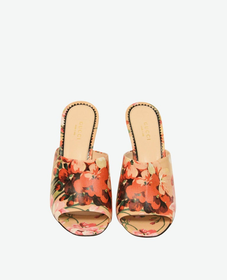 These pre-owned Gucci mules are new and never been worn . Crafted from textured leather, these heeled mules are coated with an Oriental-inspired floral graphics in a quaint palette of peach and various pinks.  Collection: Cruise 2016  Fabric: Coated