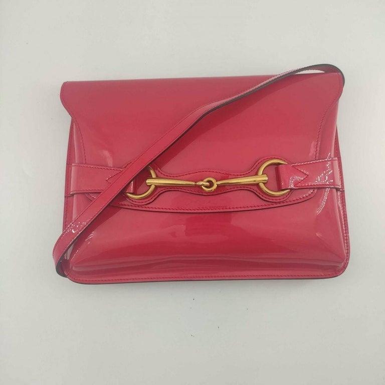 - Designer: GUCCI - Condition: Good condition. Exterior stains - Accessories: Dustbag - Measurements: Width: 27.5cm, Height: 20cm, Depth: 2cm, Strap: 115cm - Exterior Material: Patent leather - Exterior Color: Pink - Interior Material: Cloth -