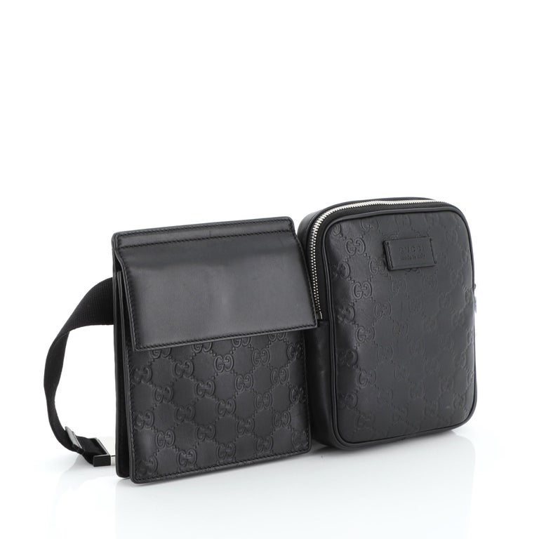 This Gucci Signature Double Waist Bag Guccissima Leather, crafted in black leather, features an adjustable waist strap, one flap bag and one zip bag and silver-tone hardware. It opens to a gray microfiber and fabric interior.  Estimated Retail