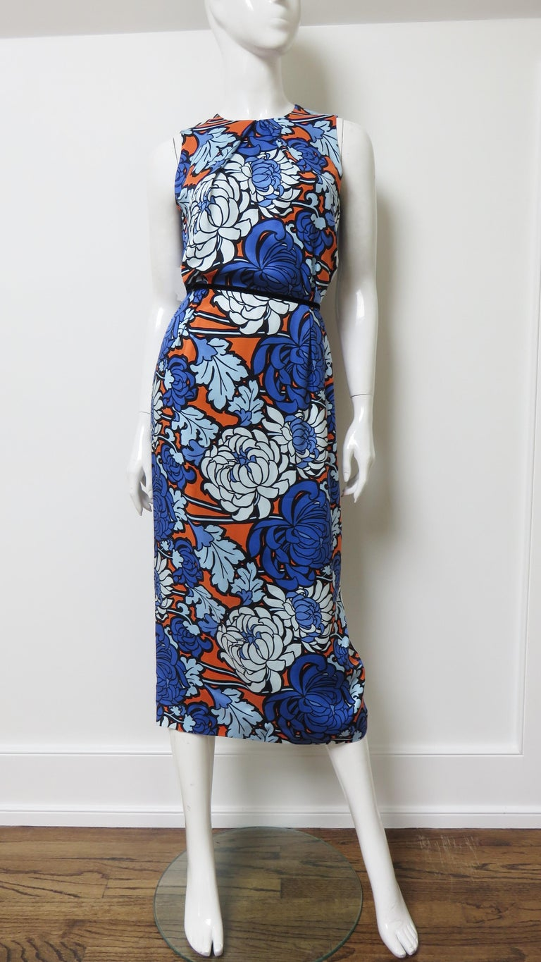 A fabulous chrysanthemum print silk dress in shades of blue and and orange.  It is sleeveless with a crew neckline and a midi length straight skirt with a back kick pleat.  The dress is fully lined in silk and has back zipper. Fits sizes Small,