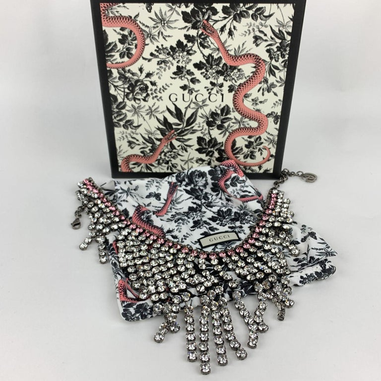 Beautiful sparkling silver metal crystal fringe bib necklace by Gucci. The necklace features pink and clear crystal trimmed with small aged silver studs. Lobster closure with GG - Gucci charm at the end of the necklace. Adjustable. Total length: 24