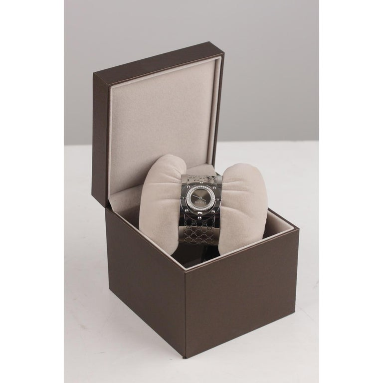 Gucci 'The Twirl' stainless steel wrist watch. Stainless steel rotating dial sith 37 diamonds (0.51 carat) set on bezel. Sapphire crystal. Quartz movement. Stainless steel bangle wristband with deployment buckle. 30 Meters / 100 Feet
