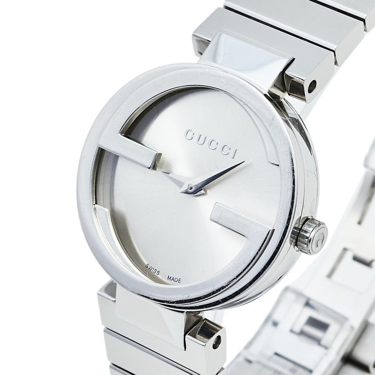 This classy Gucci watch combines beauty and femininity. Its round case features an interlocking G-shaped bezel, signifying the brand's initials. The silver dial is combined with matching hands and its minimalist style is taken further with the brand