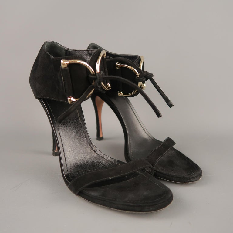 GUCCI sandals come in black suede with a thin toe strap, covered stiletto heel, and thick ankle strap, detailed with oversized, embossed D loops with tie closure. With dust bag. Made in Italy.   Very Good Pre-Owned Condition. Marked: UK 9B