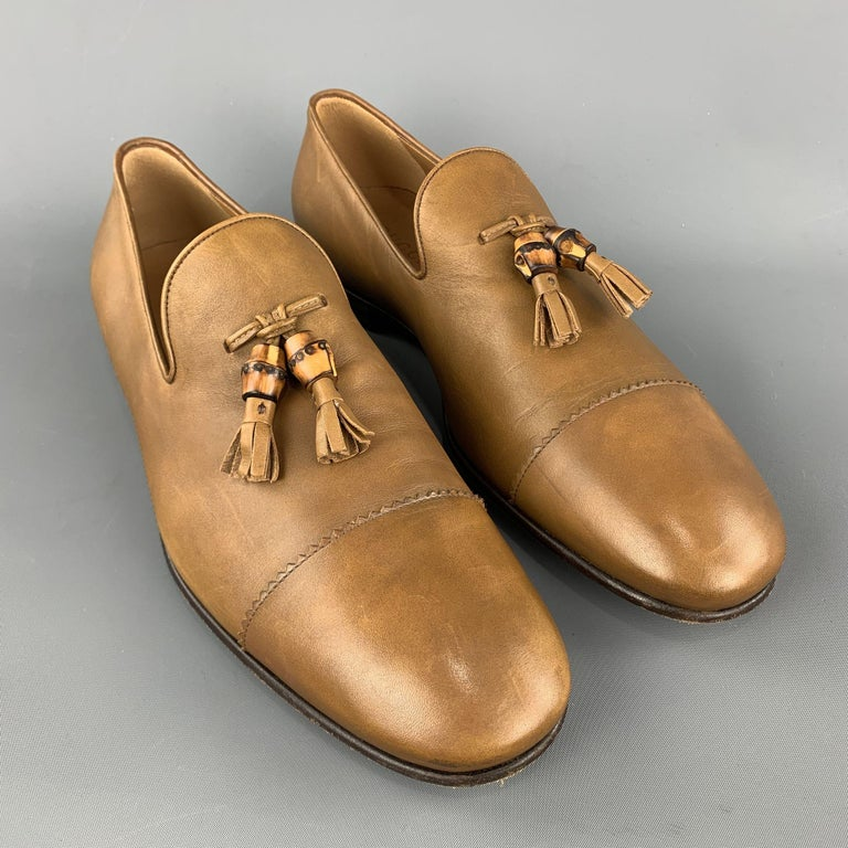 GUCCI loafers comes in a tan leather featuring a slip on style, front tassel details, and wooden sole. Made in Italy.     Excellent Pre-Owned Condition. Marked: 10  Outsole: 4 in. x 12 in.
