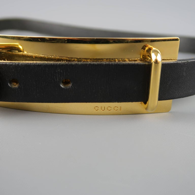 GUCCI belt comes in black leather with an oversized gold tone metal plate detail with buckle. Wear throughout. As-is. Made in Italy.   Fair Pre-Owned Condition. Marked: 90   Length: 44 in. Width: 1 in. Fits: 33.37 in. Buckle: 7.75 x 1.5 in.