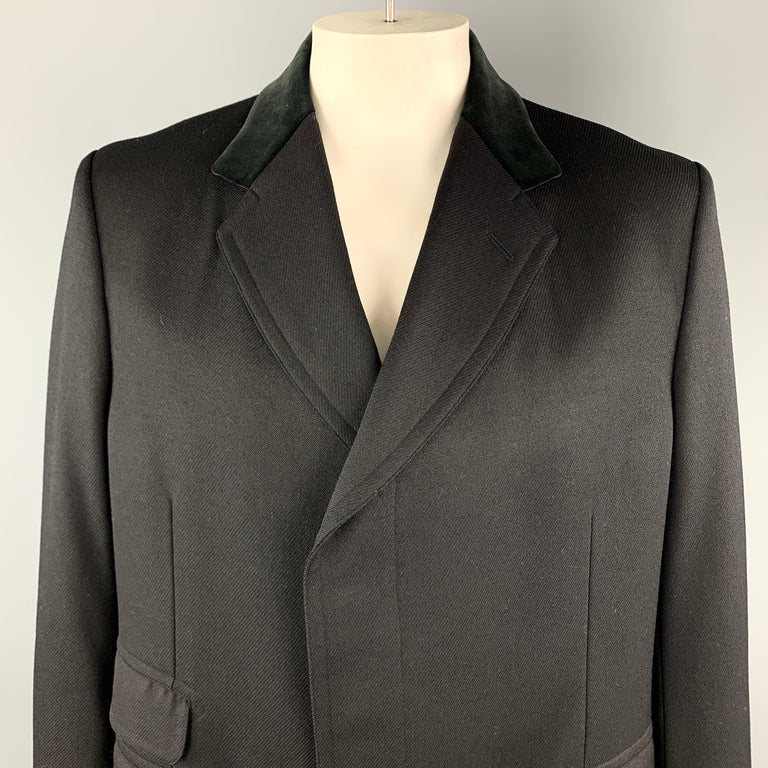 GUCCI Long Coat comes in a black solid wool material, with a velvet collar, hidden buttons at closure, single breasted, flap pockets, buttoned cuffs, and a single vent at back. Made in Switzerland.   Excellent Pre-Owned Condition. Marked: IT 56