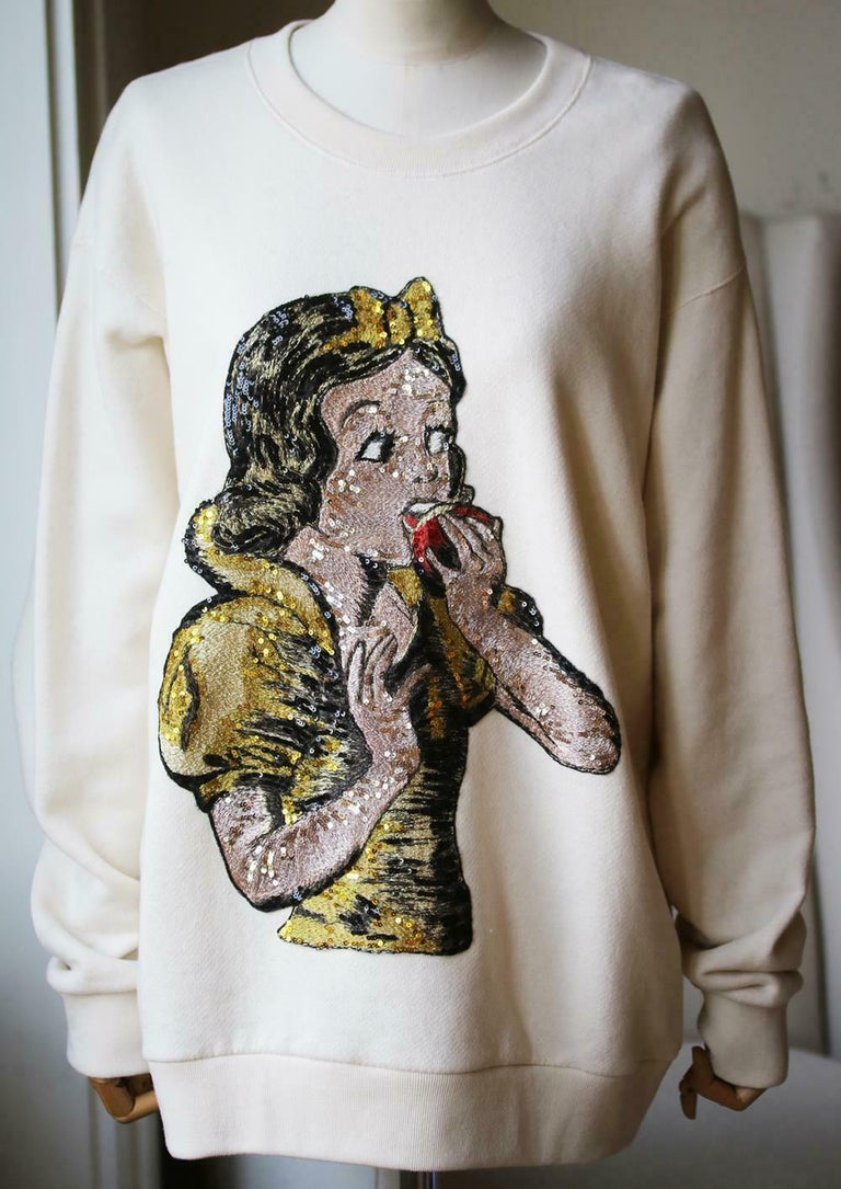 Disney character snow white is inlaid on the front of this sweater and embellished with iridescent sequins. Gucci logo on the back. Sequin embroidered cream cotton jumper with sequin embroidery. 100% Cotton.  Size: Medium (UK 10, US 6, FR 38, IT