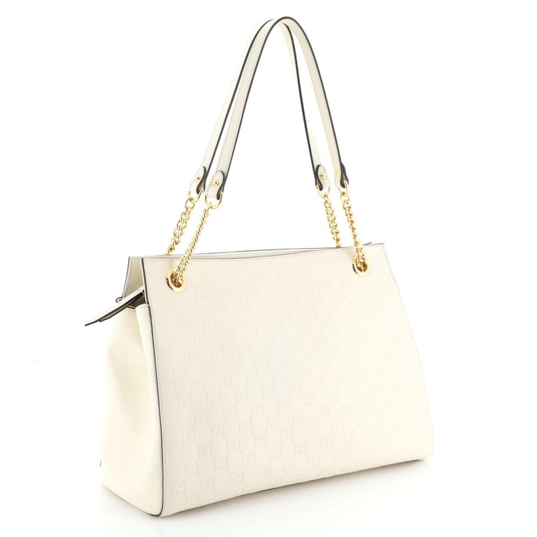 This Gucci Soft Signature Shoulder Bag Guccissima Leather Large, crafted from white guccissima leather, features chain-link shoulder straps with leather pads and gold-tone hardware. Its zip closure opens to a neutral microfiber interior with side