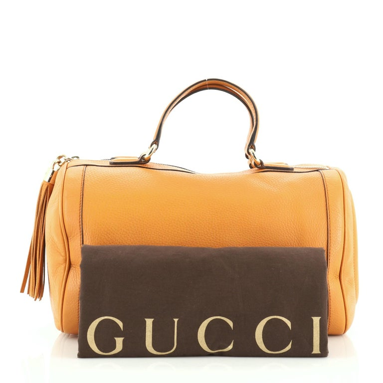 This Gucci Soho Boston Bag Leather, crafted in orange leather, features dual flat handles, tassel zipper pull accent, stitched GG logo at the side, protective base studs and gold-tone hardware. Its zip closure opens to a neutral fabric interior with