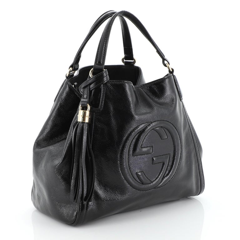 This Gucci Soho Convertible Shoulder Bag Patent Small, crafted from black patent leather, interlocking GG logo stitched at the front, dual looped top handles, protective base studs, and gold-tone hardware. Its hook clasp closure opens to a black
