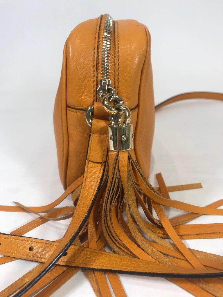 Orange grained leather. Gold-tone hardware. Zip closure at top. Single adjustable flat shoulder strap. Stitched interlocking GG logo accent front. Creme canvas lining. Dual interior slit pockets. Featuring tassel-embellished.