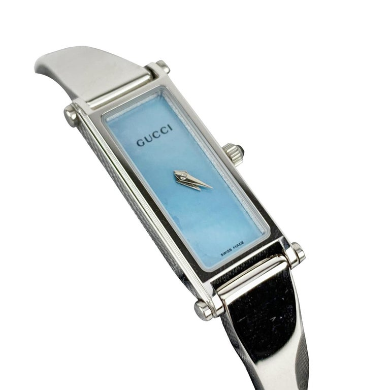 Gucci stainless steel ladies wrist watch. Model 1500L. Stainless steel case. Quartz movement. Water Resistant (up to 3 ATM). Light blue mother of pearl dial. Swiss Made. Gucci written on the face, clasp & reverse. Clasp with snap closure (see