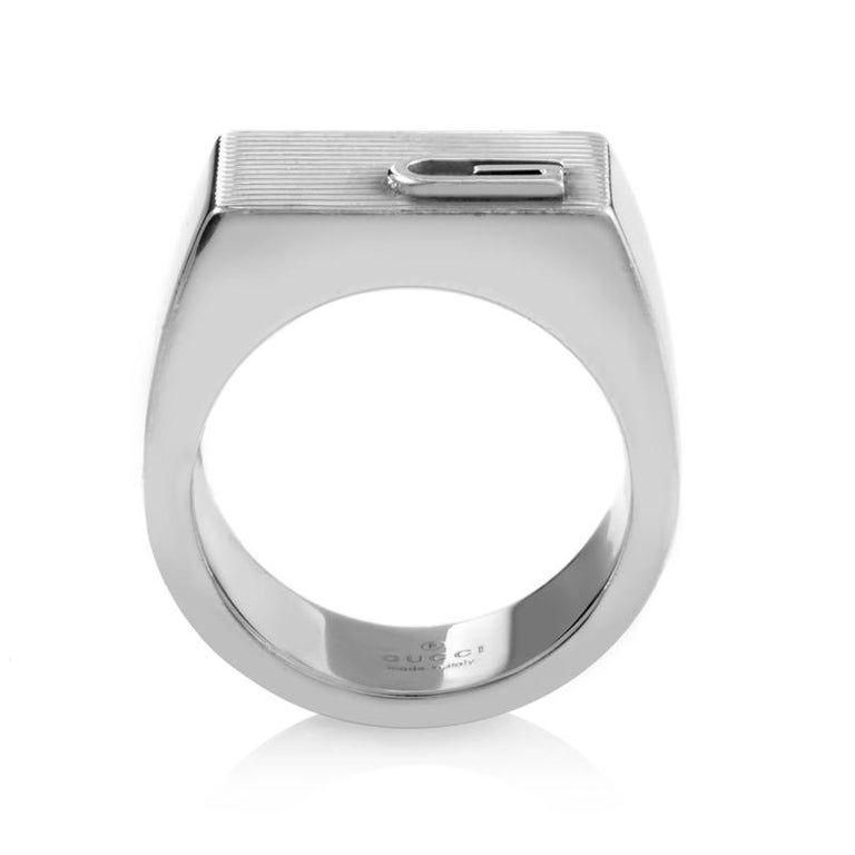 This exceptionally stylish signet ring from Gucci is a classic ring in every sense of the word. It is elegantly crafted in attractive sterling silver with the band forming an oblong ridged platform as the chic setting and a trademark Gucci initial