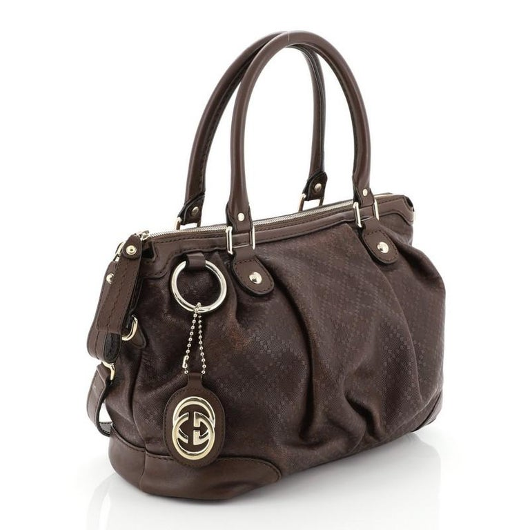 This Gucci Sukey Top Handle Satchel Diamante Leather Medium, crafted from brown diamante leather, features dual rolled handles and gold-tone hardware. Its two-way zip closure opens to a neutral fabric interior with side zip and slip