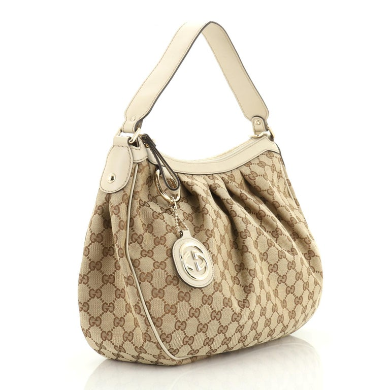 This Gucci Sukey Tote GG Canvas Medium, crafted from brown GG canvas, features dual rolled leather handles, leather trim, and gold-tone hardware. Its magnetic snap closure opens to a neutral fabric interior with side zip pocket.  Estimated Retail
