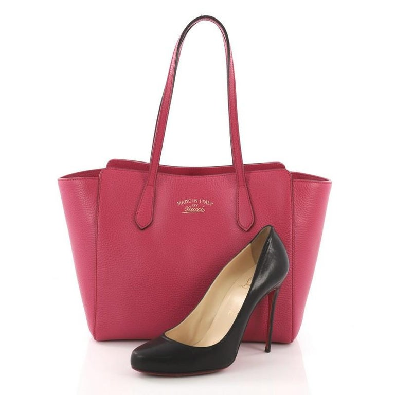 This Gucci Swing Tote Leather Small, crafted in pink leather, features dual slim handles, Gucci stamped logo at the front, expanded wing silhouette, and gold-tone hardware. Its hidden magnetic snap closure opens to a beige fabric interior with side