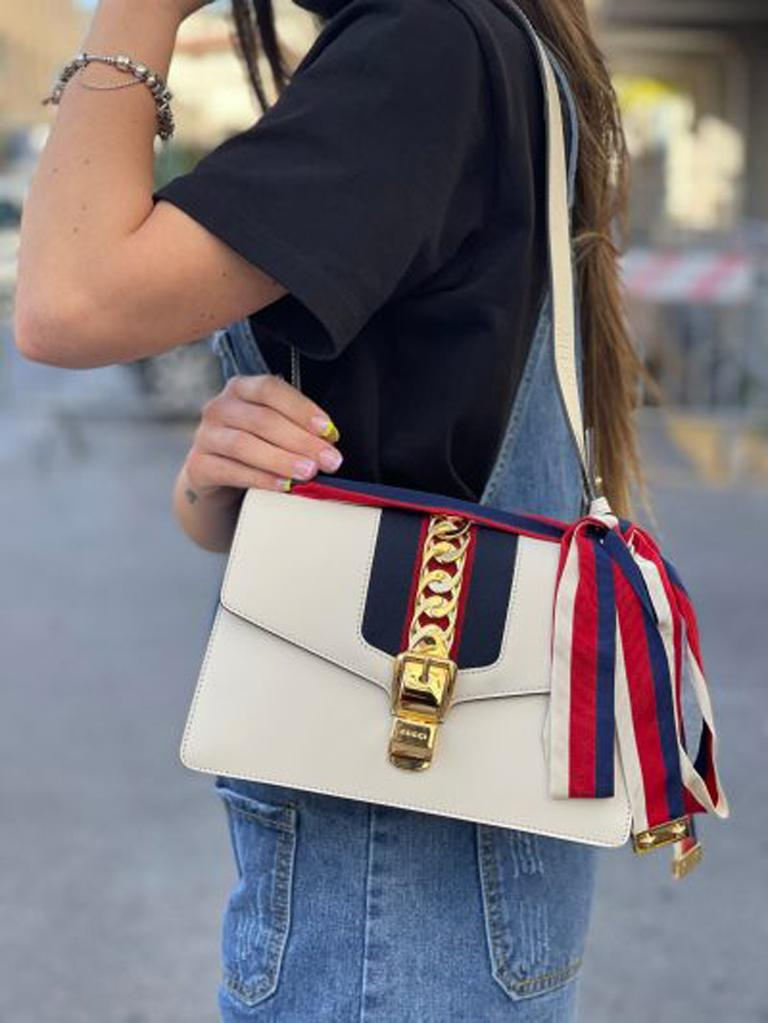 Gucci Sylvie model bag made of white leather with golden hardware. Hook closure, internally lined in white leather, quite roomy. Equipped with a leather handle to wear it on the shoulder. The bag is in excellent condition.  Dimensions: 6 × 22 × 17 cm