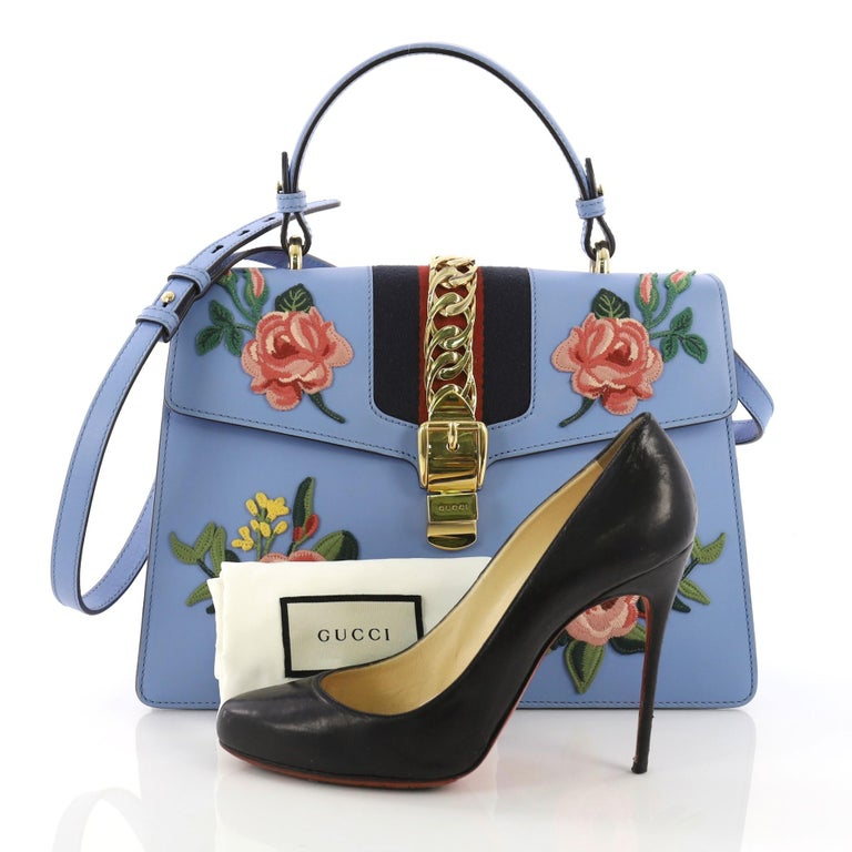 8b29186d9 This Gucci Sylvie Top Handle Bag Embroidered Leather Medium, crafted in  blue embroidered leather,