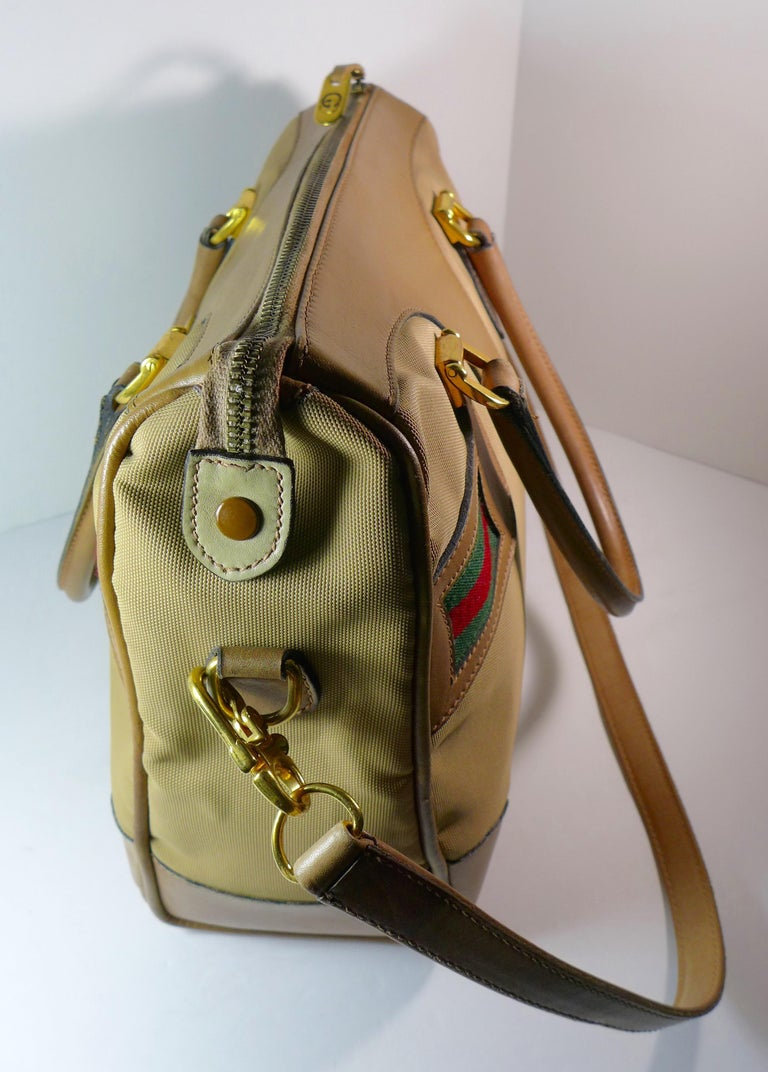 This spacious Gucci tan leather and canvas bag features a leather shoulder strap, leather handles, gold hardware, and the iconic green and red stripes. The bag has a zipper closure and inside zip pocket.   Measurements in Inches:  Height: 11 Length: