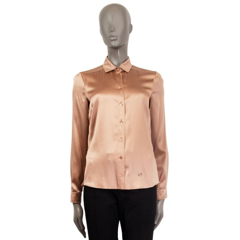 100% authentic Gucci satin long sleeve shirt in tan silk (96%) and elastane (4%). Closes with eight buttons on the front and with a GG silver-tone metal logo on the left-side bottom. Unlined. Has been worn and is in excellent