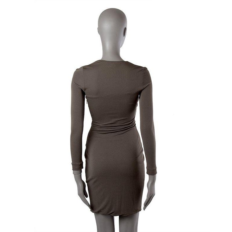 Gucci long-sleeve wrap dress in taupe jersey with v neck and front draping held by a golden rectangular metal fixture. Closes with invisible side zipper. Lined in matching fabric. Has been worn and is in excellent condition.  Tag Size XS Size