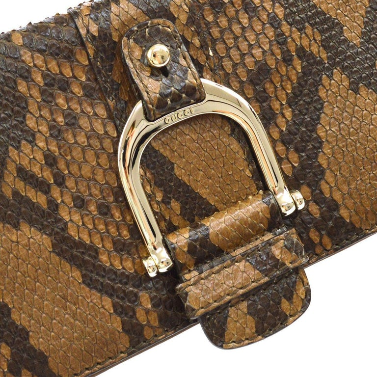 Snakeskin Leather Gold tone hardware Canvas lining Snap closure at front flap Made in Italy Measures 11.5
