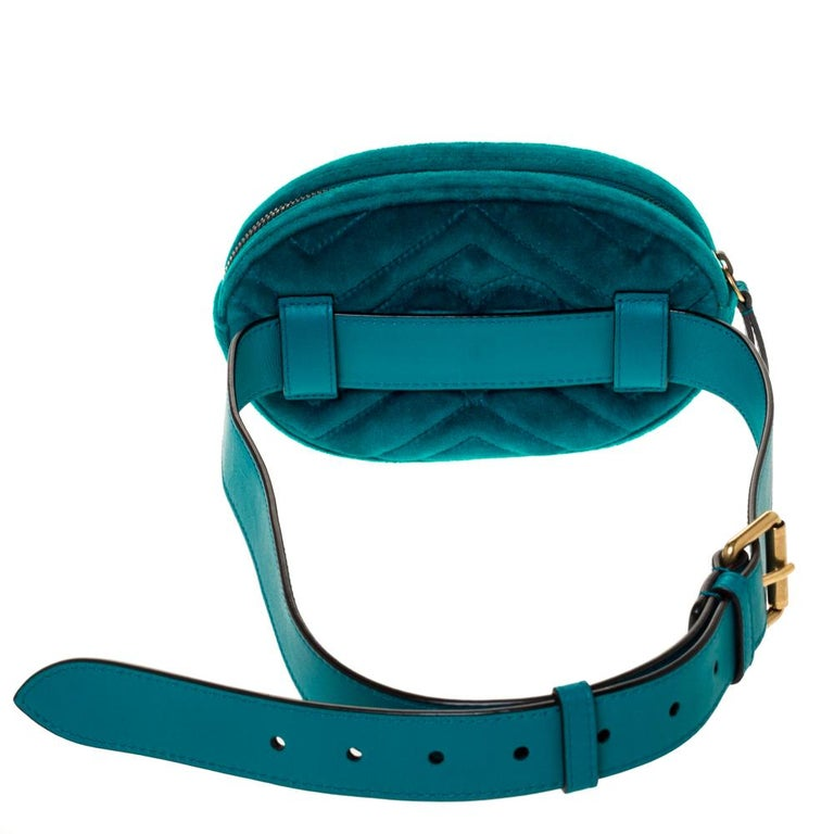 The Gucci Marmont bag has been exquisitely crafted in Italy and made from teal-hued velvet featuring the signature Matelasse pattern all over. It is equipped with a luxurious satin interior that is secured with zip closure. On the front, there is