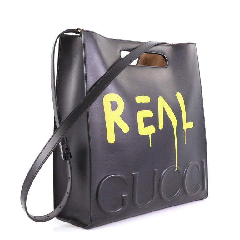 This Gucci Tote GucciGhost Leather Medium, crafted from black leather, features cutout top handles, GucciGhost print, debossed logo across baseline and aged gold-tone hardware. Its wide open top showcases a beige microfiber interior.   Estimated