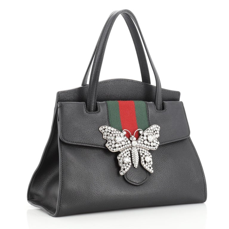 This Gucci Totem Top Handle Bag Leather Medium, crafted from black leather, features dual leather top handles, web stripe with crystal butterfly ornament, and aged silver and gold-tone hardware. Its press-lock closure opens to a neutral microfiber