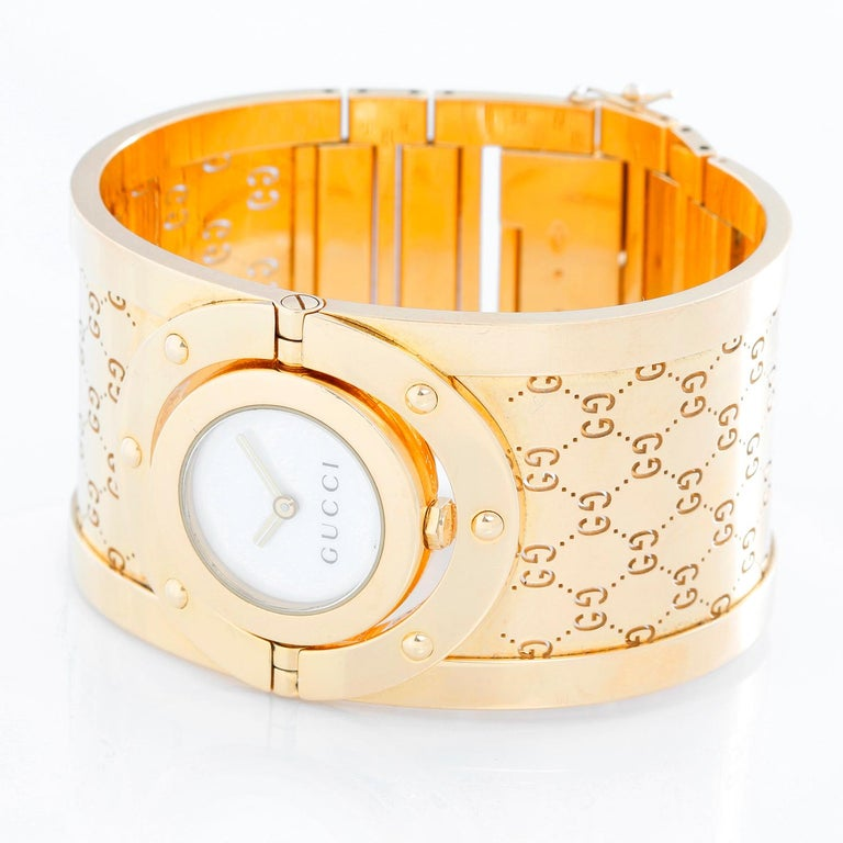 Gucci Twirl 18k Yellow Gold  Ladies Watch - Quartz. 18K Yellow gold ( 33 mm ) . Mother of Pearl dial . 18K Yellow gold cuff bracelet; fits up to a 6 1/2 inch wrist . Pre-owned with custom box .