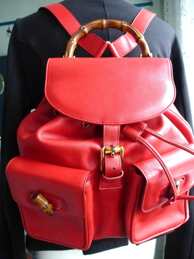 Classic luxury pre loved GUCCI two pocket backpack with iconic bamboo details in red leather.   Measurement:  Height 30 cm, Width 37 cm around 74 cm, Deep 10 cm, 2 rear straps 80 cm maximal, pockets on the front H 14 cm x 11 cm . The backpack is in