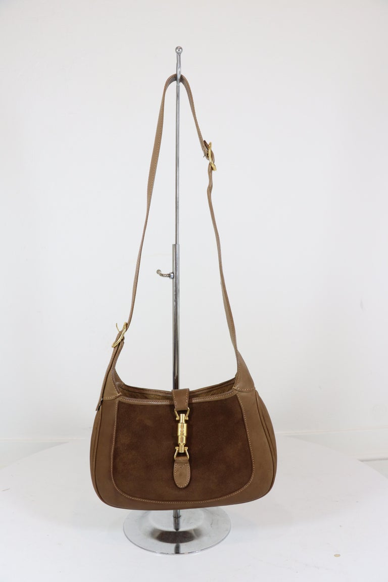 Gucci 1970's vintage small Jackie O bag,  in medium brown suede with brown calf leather trim and handle and a gold-tone piston clasp closure at the front. Interior is fully lined with one zippered pocket. Bag includes a matching leather extension