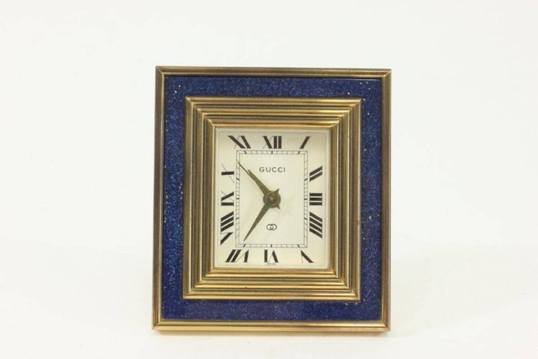 Gucci 8-day travel clock. Clock has a blue lapis enamel insert. Nicely designed with a retractable stand. A great collector's item. In working order.