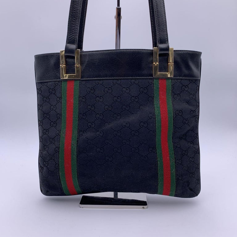 Beautiful Gucci tote made in black monogram canvas with genuine leather trim. Green/Red/Green striped canvas shoulder straps. 2 compartments and 1 middle zip compartment. 'Made in Italy by Gucci' embossed inside.  Details  MATERIAL: Canvas  COLOR: