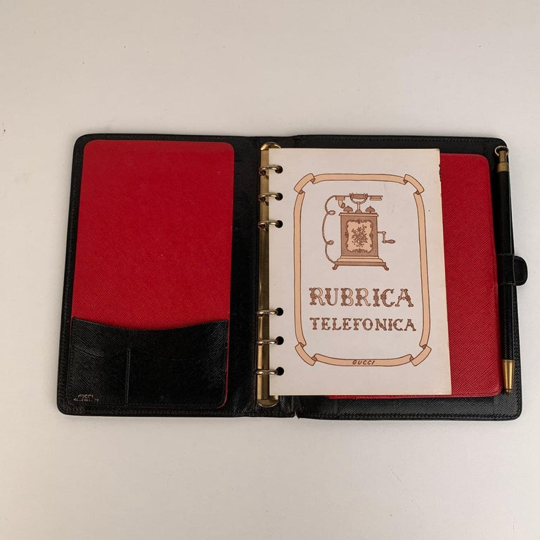 Elegant vintage agenda cover by GUCCI crafted in black eather. Red and black leather interior. It features a six ring binder. Mechanical pencil included. 2 side open slots inisde. 'GUCCI - Made in Italy' embossed inside.     Details  MATERIAL: