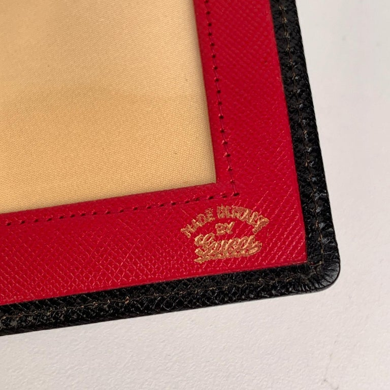 Rare vintage GUCCI folding picture display/photo holder. This item is ideal for travel, it is small and portable. Crafted in black leather with button closure. Inside, it is lined with gold-ton satin fabric and red leather with clear plastic window