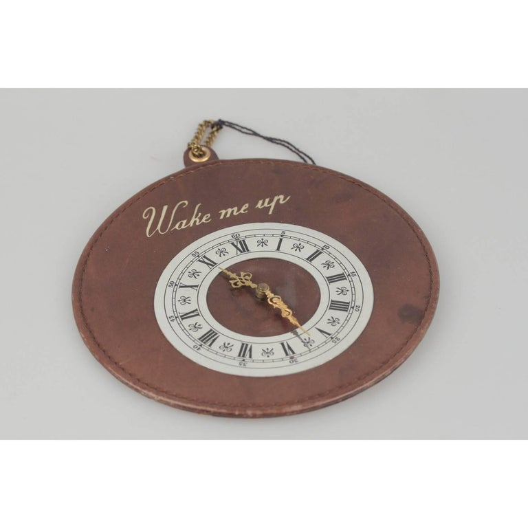 - Rare GUCCI vintage waking up door sign  - Brown leather disk with mock clock - 'Wake me up' writing embossed on the front - Marked 'Made in Italy by GUCCI' on the back - Diameter: 5.75 inches - 14,6 cm