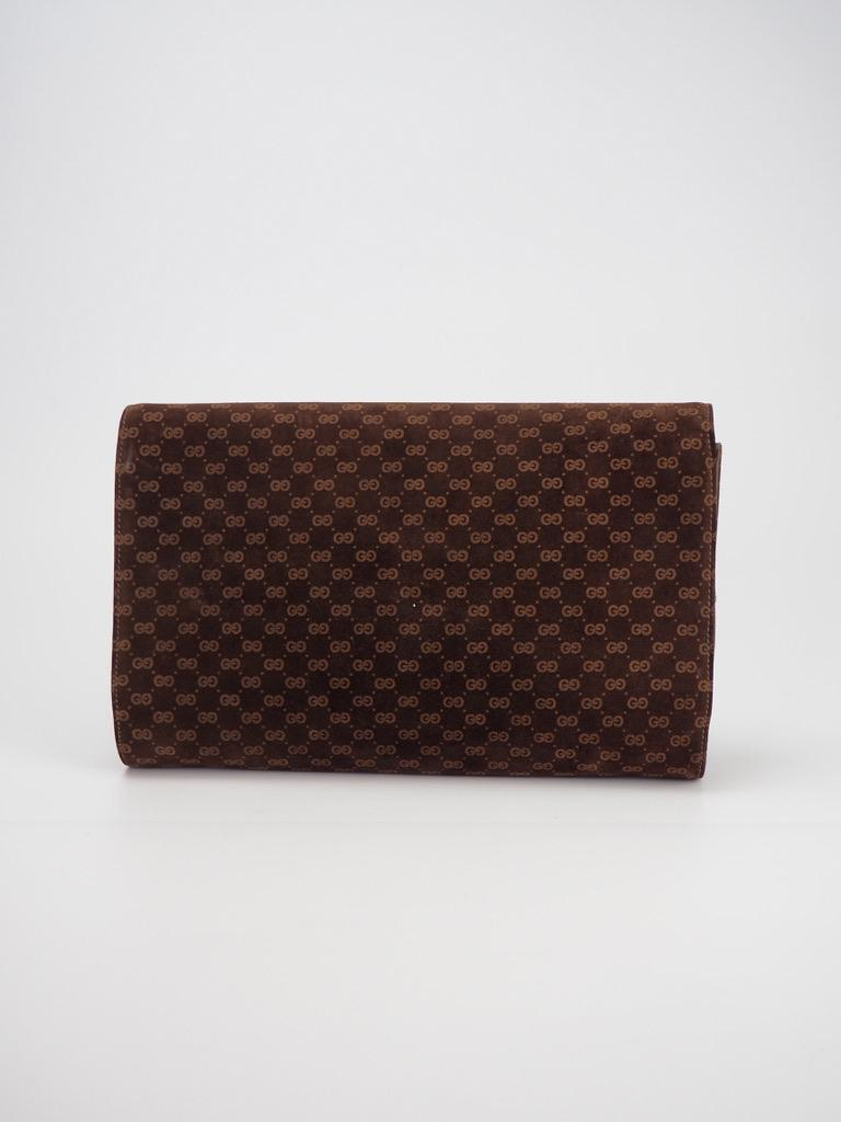 """This vintage Gucci clutch is made of brown suede with Gucci's signature GG monogram print and features brown leather finishes, a front flap with leather detail and a yellow leather interior.  COLOR: Brown MATERIAL: Suede MEASURES: H 6.5"""" x L 10"""" x D"""
