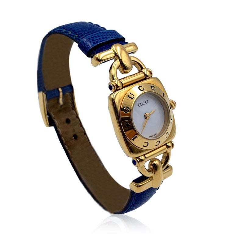 Gucci 6300 L Gold plated stainless steel wrist watch from the 90s. White dial and Sapphire crystal. Swiss Made Quartz movement. Gucci written on face and on the bezel .Water Resistant. Blue leather trap with buckle closure (GG logo engraved on the