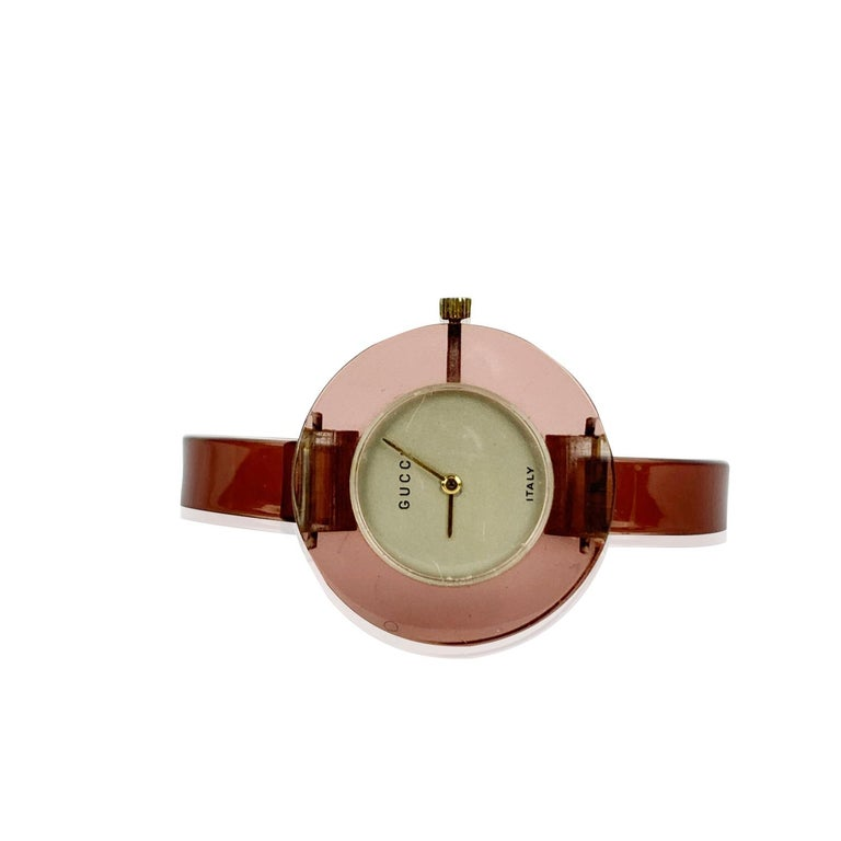 Beautiful vintage bangle wristwatch by GUCCI in translucent pink lucite. 17 Jewels Swiss Wind-Up. Light gold dial. Clasp closure. 'GUCCI' and 'Italy' embossed on the dial. Bracelet diameter: 2.25 Inches - 5,8 cm. Case diameter: 35 mm (38 mm