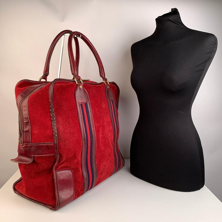 Vintage travel bag by GUCCI, crafted in burgundy red suede with genuine leather trim and handles. Blue/red/blue signature web striped detailing on the front and on the back. Upper zipper closure + security key-lock closure (key is missing). 5 bottom