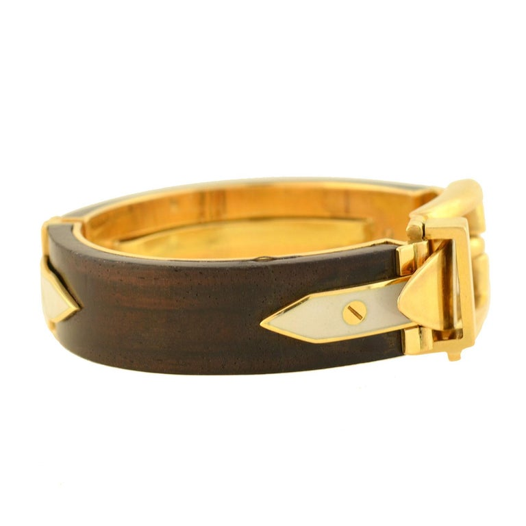 A gorgeous and rare signed Vintage Gucci bangle bracelet from the 1970s era! This 18kt yellow gold piece features a stunning functional buckle design at the front, allowing it to easily open and close and adjust in size. Two curved pieces of