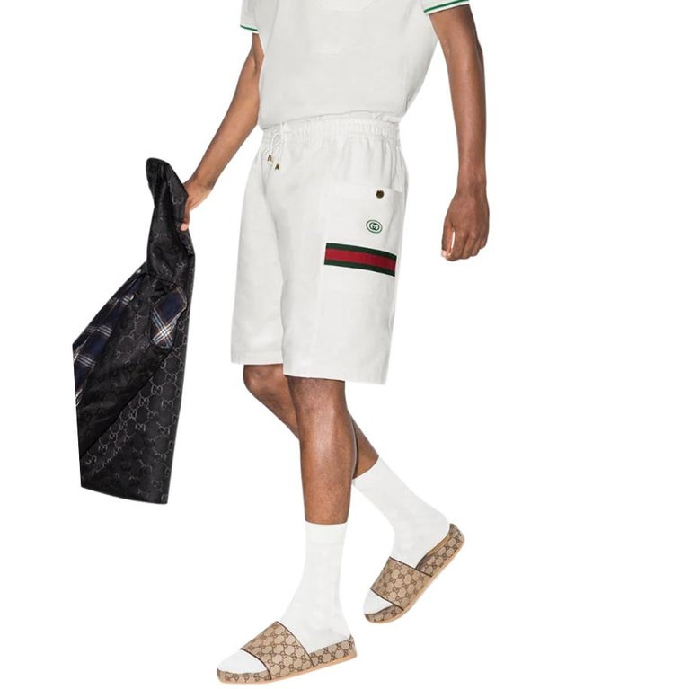 Gucci Web Stripe Cotton Track Shorts  -White Cotton Body - elasticated waist with drawstring - Two patch pockets with gold tone button - Web stripe detail to pockets & GG Embroidery  Mid weight, fits true to size with a relaxed fit.  Body: Cotton