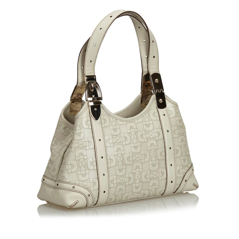 This shoulder bag features a horsebit print on leather body, flat leather handles, open top, and interior zip pockets. It carries as B+ condition rating.  Inclusions:  This item does not come with inclusions.  Dimensions: Length: 17.00 cm Width: