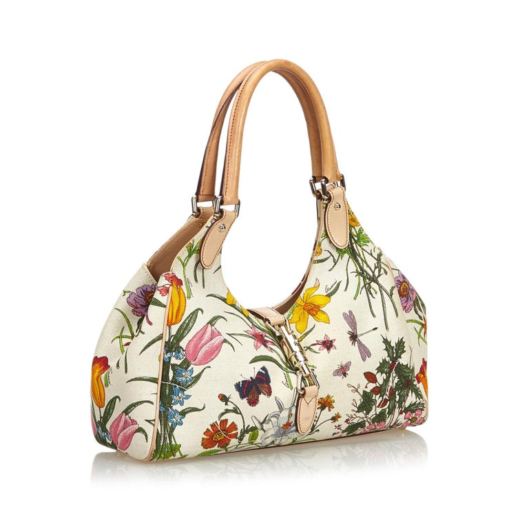 The New Jackie features a floral print on a canvas body, rolled leather straps, a leather strap with a lock closure, and an interior zip pocket. It carries as B condition rating.  Inclusions:  This item does not come with