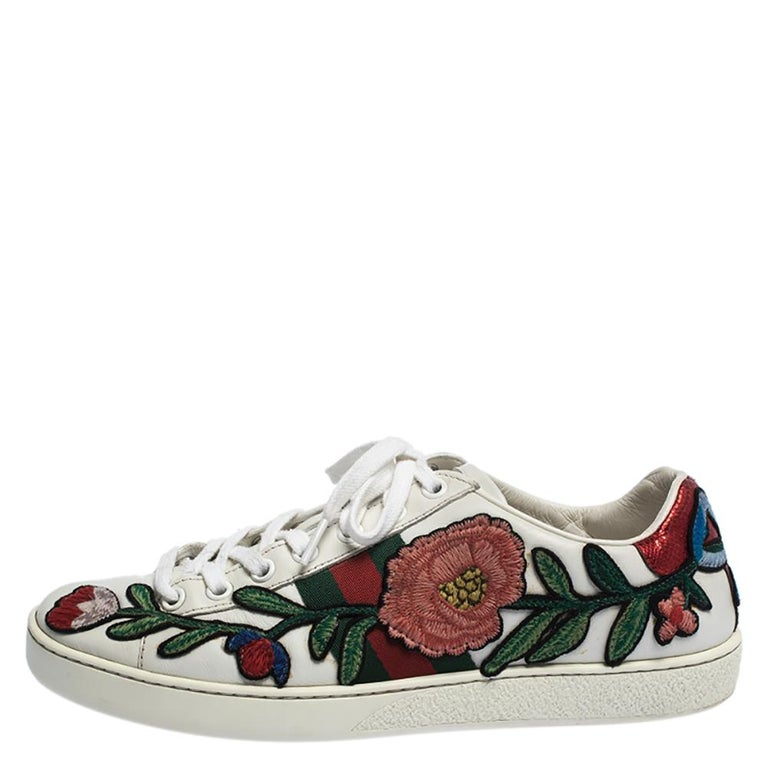 Stacked with signature details, this Gucci pair is rendered in white leather and is designed in a low-cut style with lace-up vamps. They have been fashioned with the iconic web stripes and floral embroideries. Complete with red and green snake trims