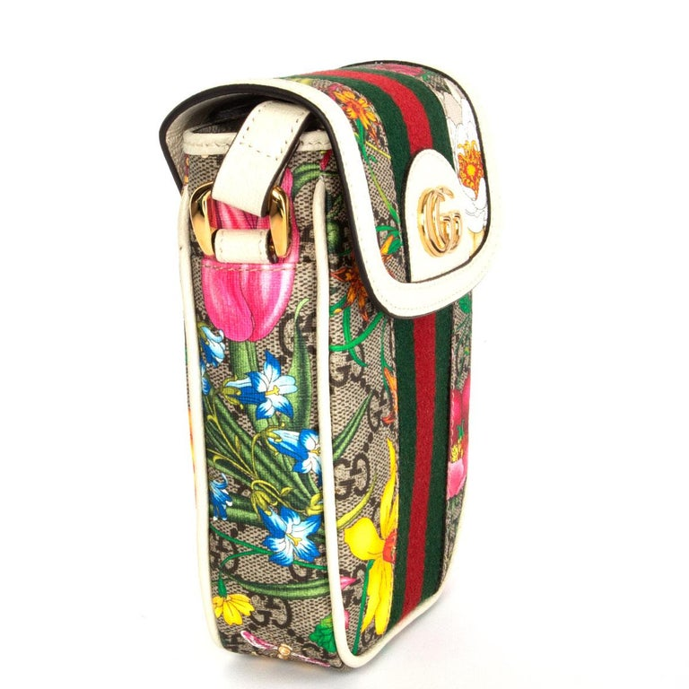 Gucci Ophidia mini phone bag in white leather and multicolored Floral GG Supreme canvas. Features an adjustable shoulder strap, a fold over front flap, a gold tone GG logo, a Web stripe down the front and an all-over Flora pattern. Has been carried